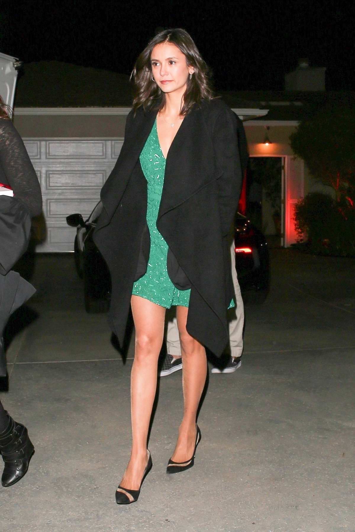 Nina Dobrev seen in a green dress with a black coat at Jennifer Klein's Holiday Party in Los Angeles