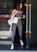 Olivia Culpo wore grey pinstriped sports bra with matching leggings as she stopped to grab post-workout smoothies at Heart and Hustle in West Hollywood, Los Angeles