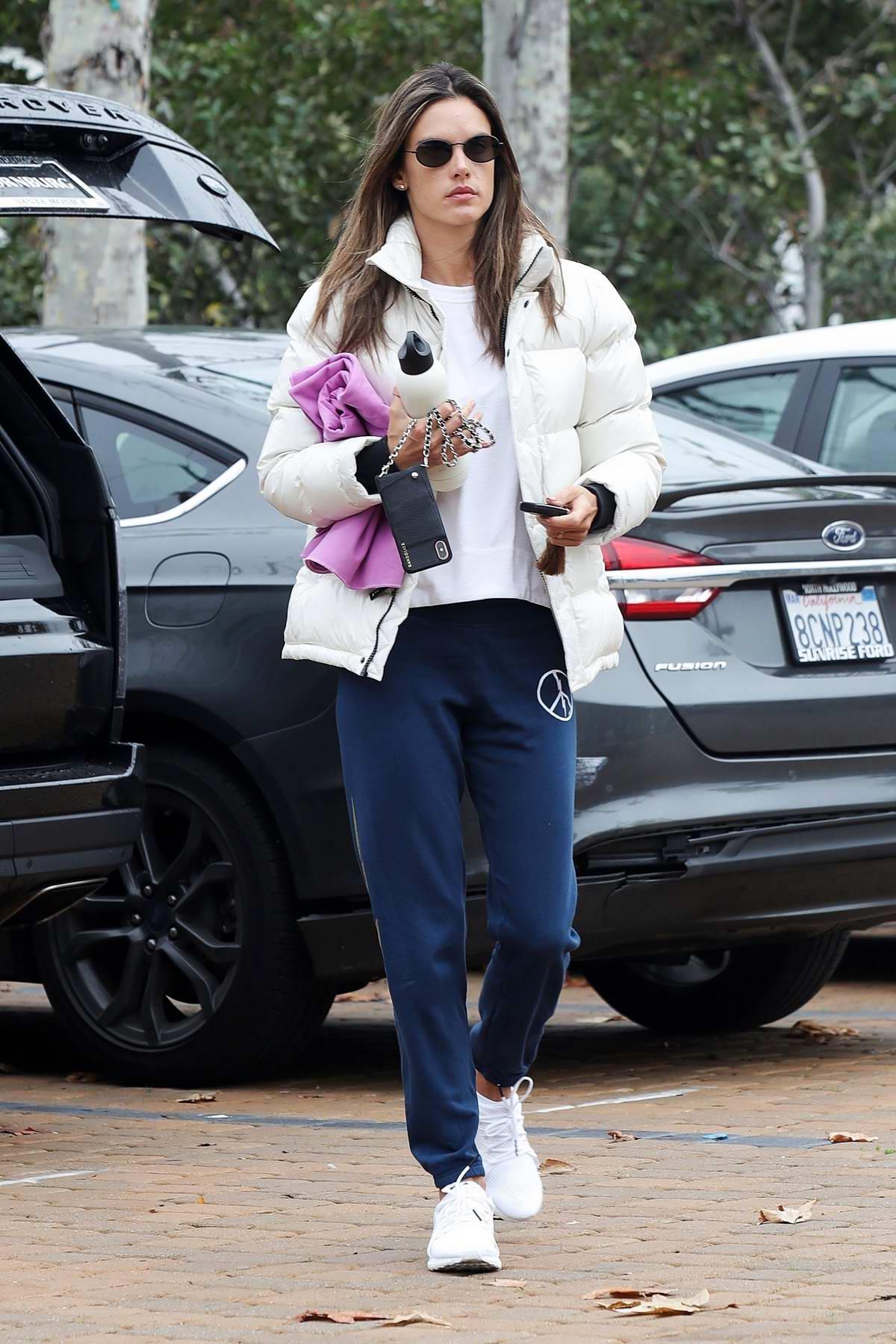 Alessandra Ambrosio rocks a white puffer jacket and blue sweatpants to her morning yoga class in Malibu, California