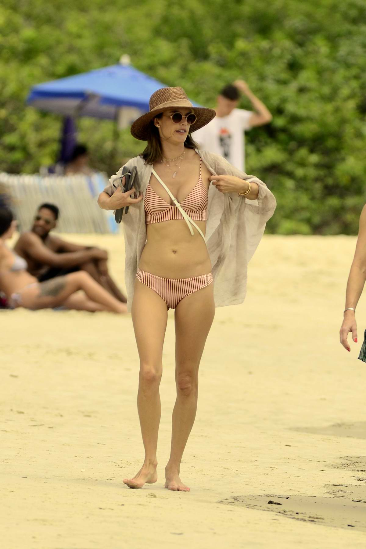 Alessandra Ambrosio seen wearing a striped bikini while enjoying a day at the beach with friends in Florianopolis, Brazil