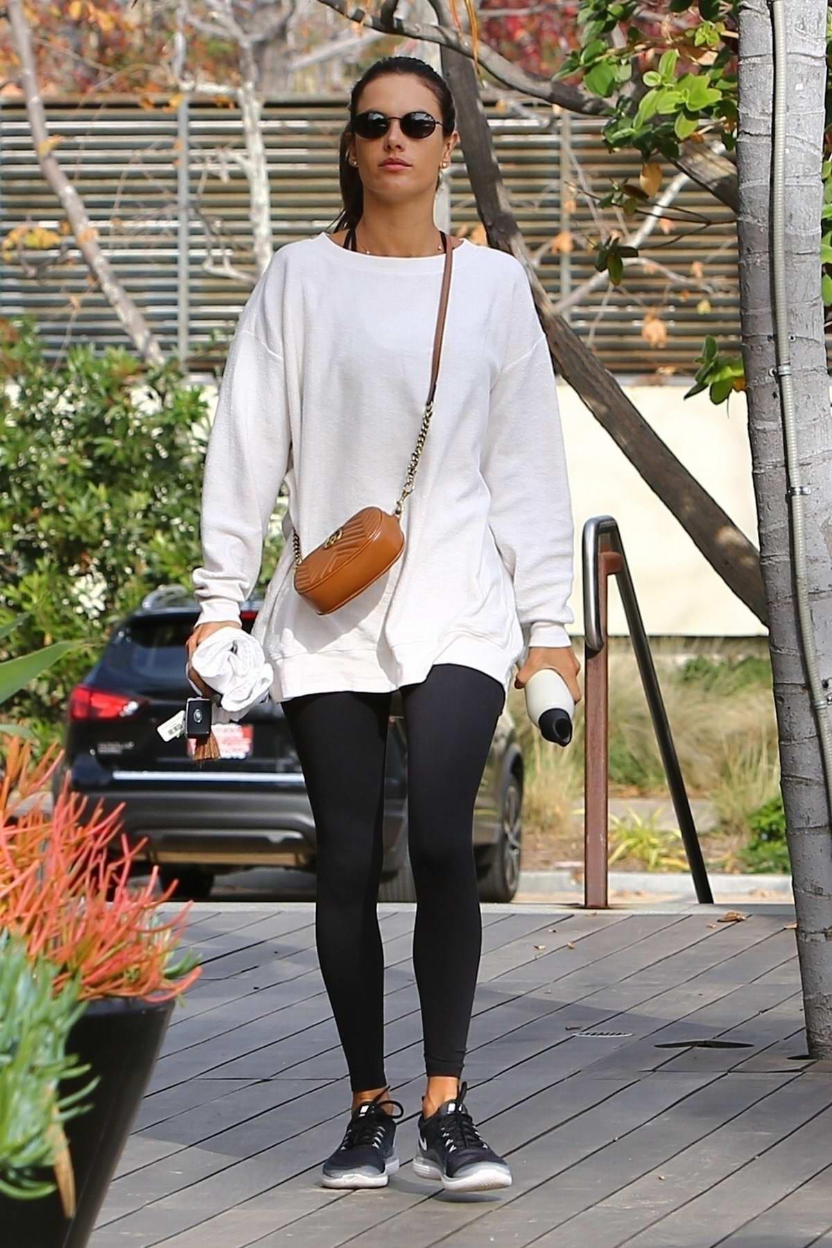 Alessandra Ambrosio wears a white sweatshirt and black leggings as she hits the gym in Malibu, California
