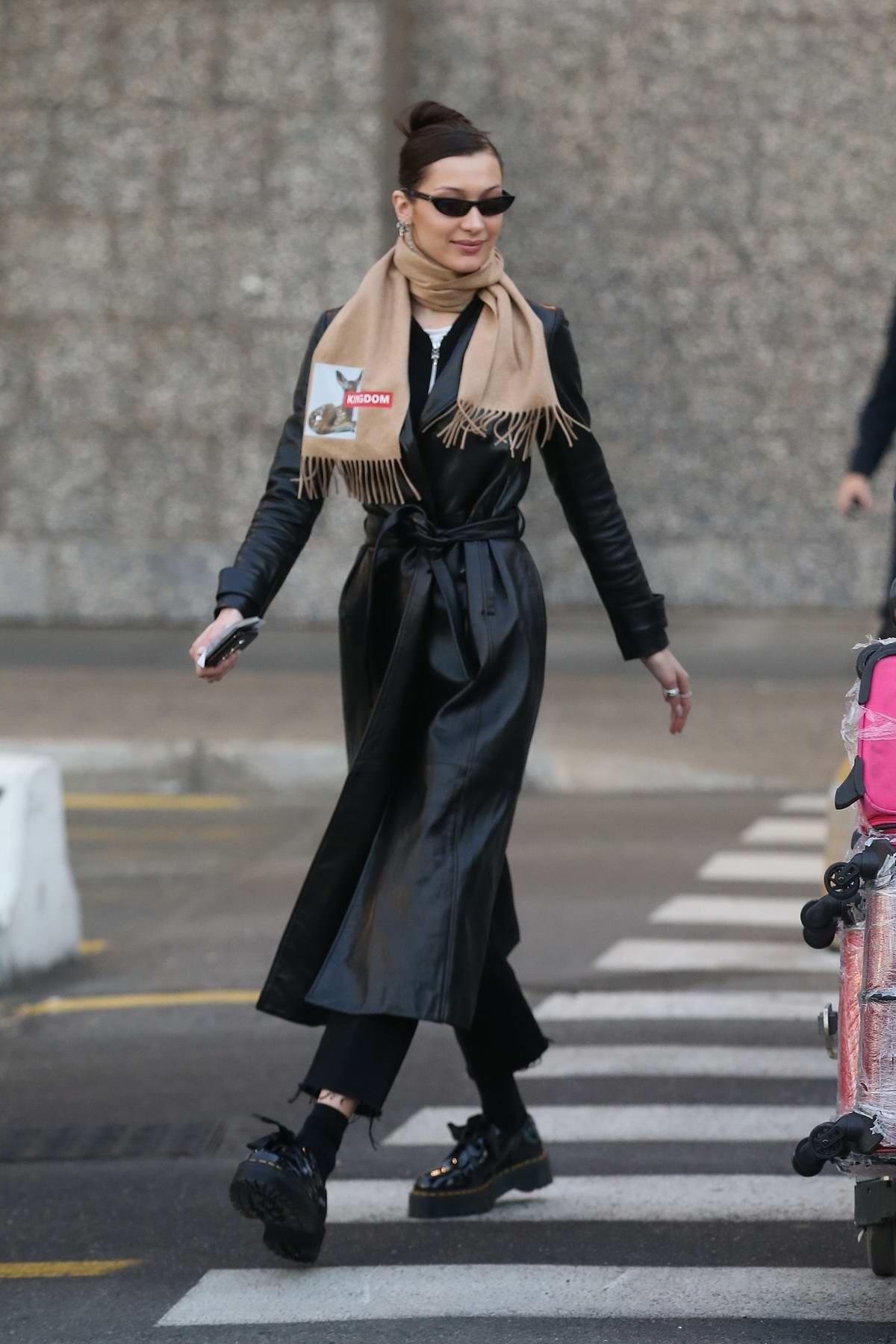 Bella Hadid wears a black leather trench coat as she touch down in Milan, Italy