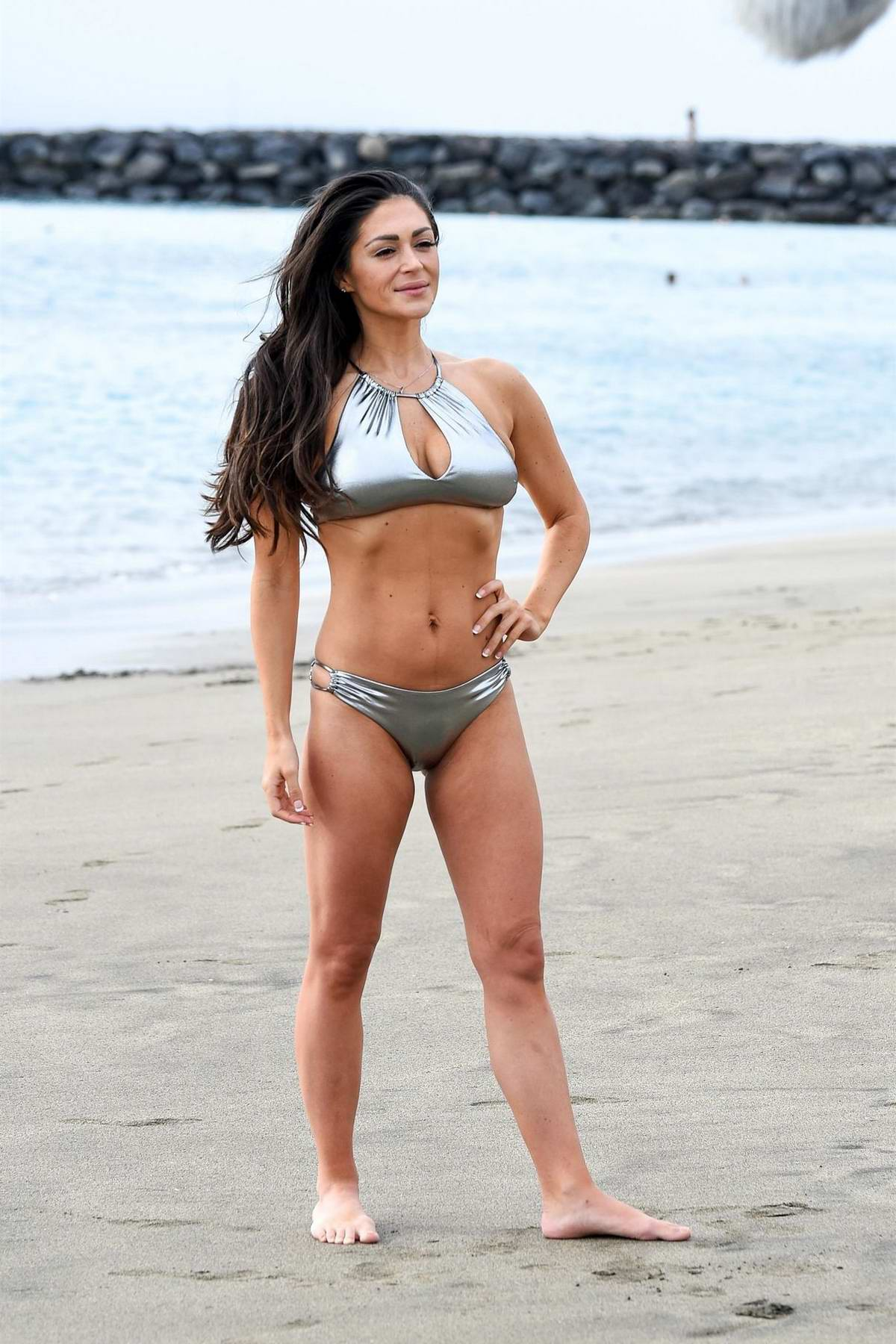 Casey Batchelor wears a metallic silver bikini while filming her Yoga Blitz app in Tenerife, Spain