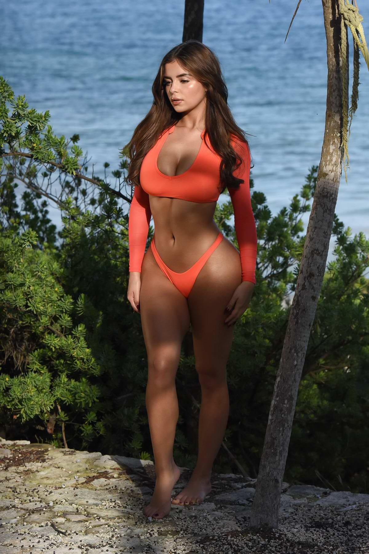 Demi Rose wears a plunging orange top and bikini bottoms during a photoshoot in Tulum, Mexico
