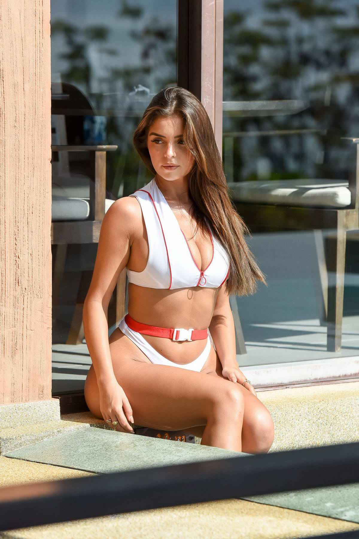 Demi Rose wears a white bikini as she relaxes by the pool while on holiday in Phuket, Thailand