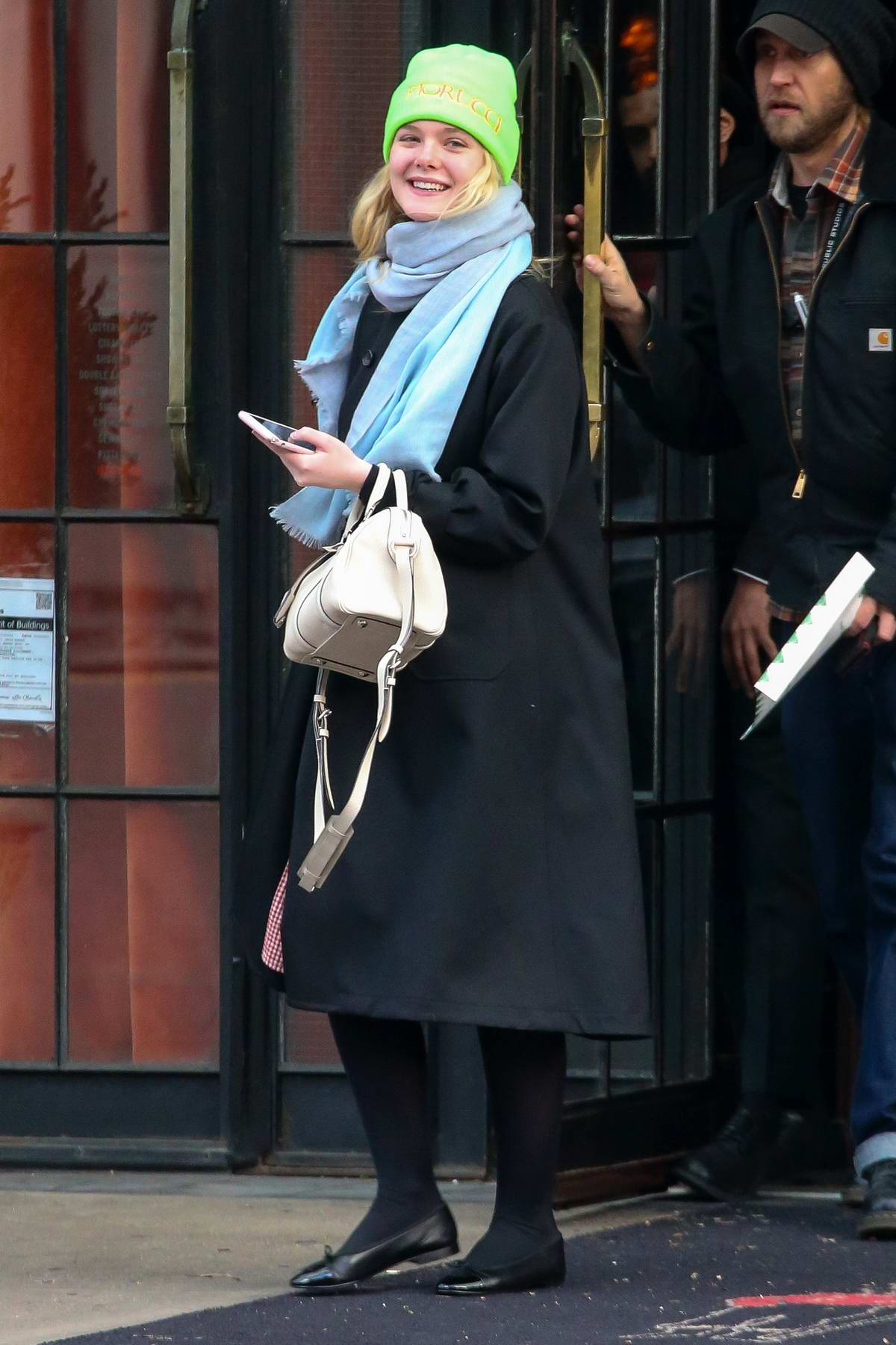 Elle Fanning is all smiles as she leaves The Bowery Hotel wearing a bright green beanie in New York City