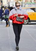 Elsa Hosk wears a colorful puffer jacket and black leggings while out running errands on chilly day in New York City