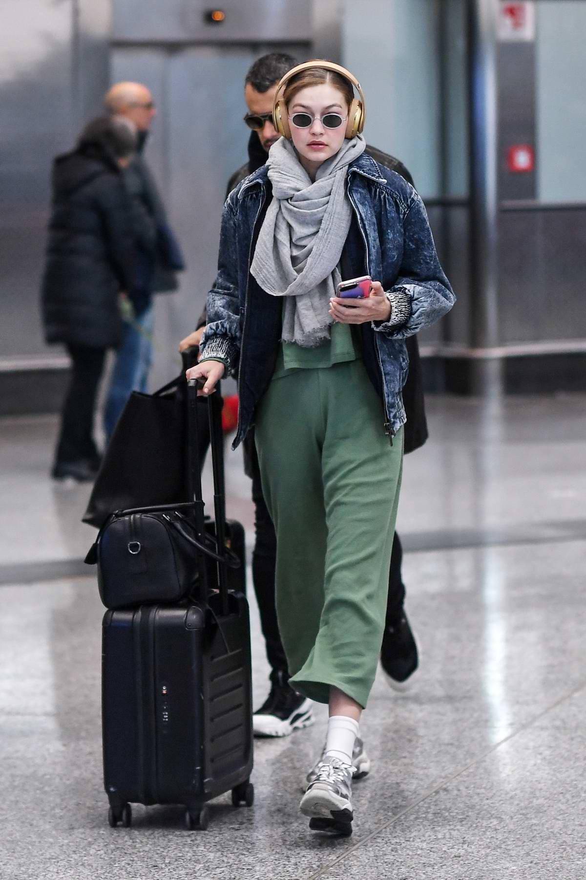 Gigi Hadid rocks her Beats headphones as she arrives at Malpensa Airport in Milan, Italy