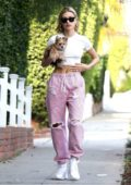 Hailey Baldwin Bieber wore a cropped white top and pink drawstring pants while running errands with her new puppy in Hollywood, California