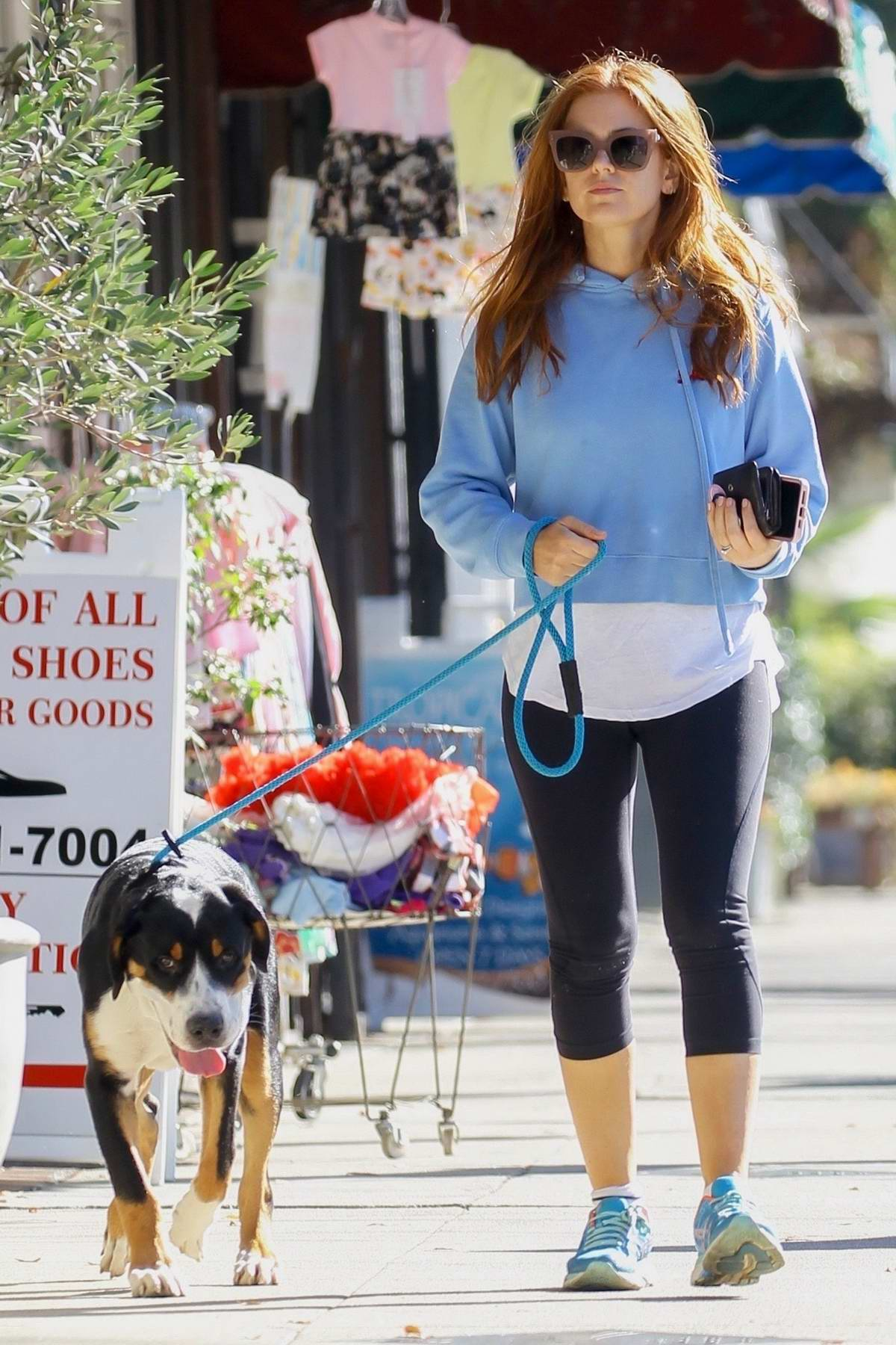 Isla Fisher wears a blue sweatshirt and black leggings during a coffee run with her dog in Studio City, Los Angeles