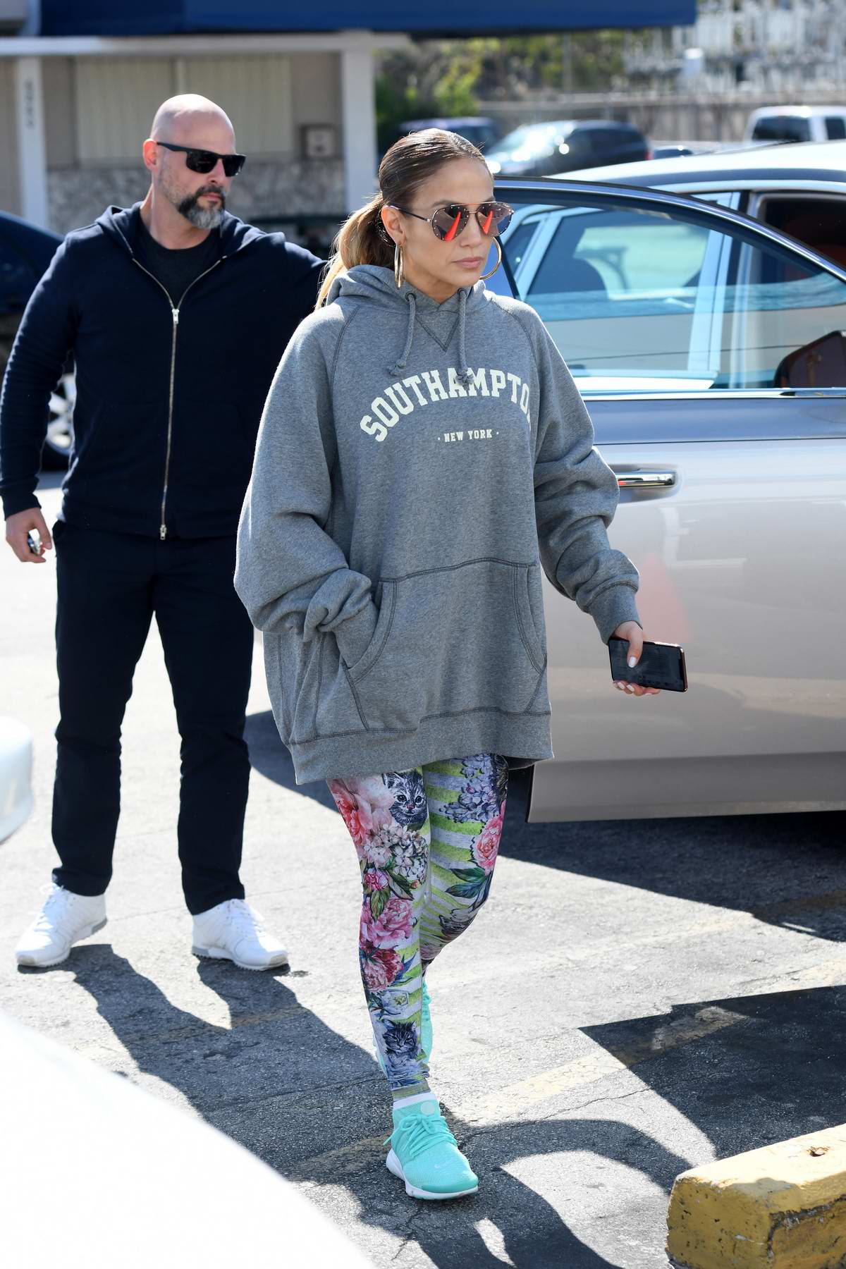 Jennifer Lopez wears an oversized grey hoodie with colorful patterned leggings as she hits the gym in Miami, Florida
