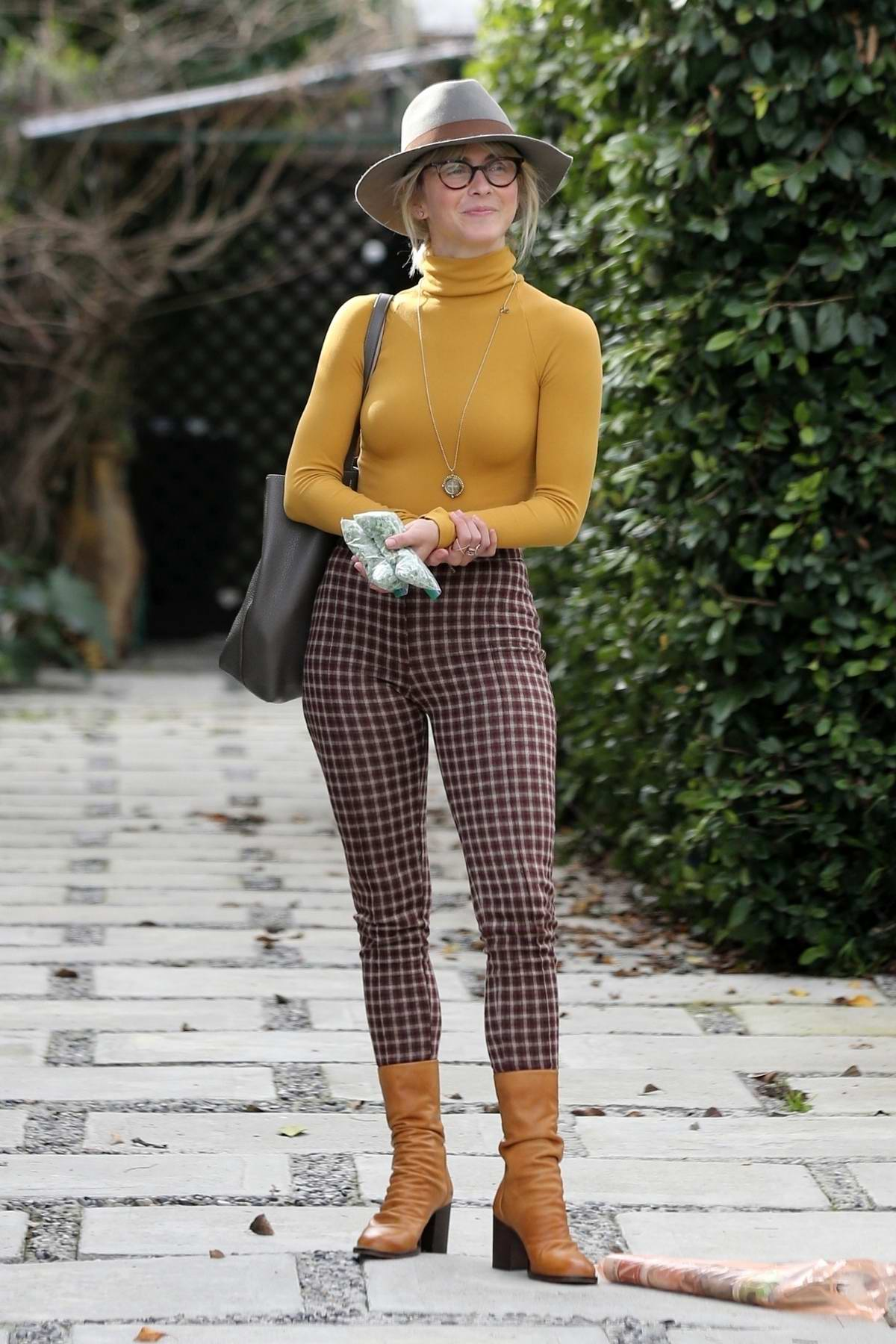 Julianne Hough looks stylish in a mustard yellow turtleneck, checkered pants with brown boots and grey fedora while out with Derek Hough in Los Angeles