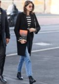 Kaia Gerber steps out holding the book 'The Great Alone' during Milan Men's Fashion Week, Italy
