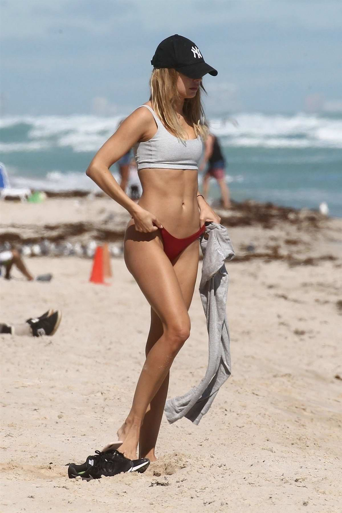 Kimberley Garner rocks a grey sports bra and red bikini bottoms while doing some beach workout in Miami, Florida