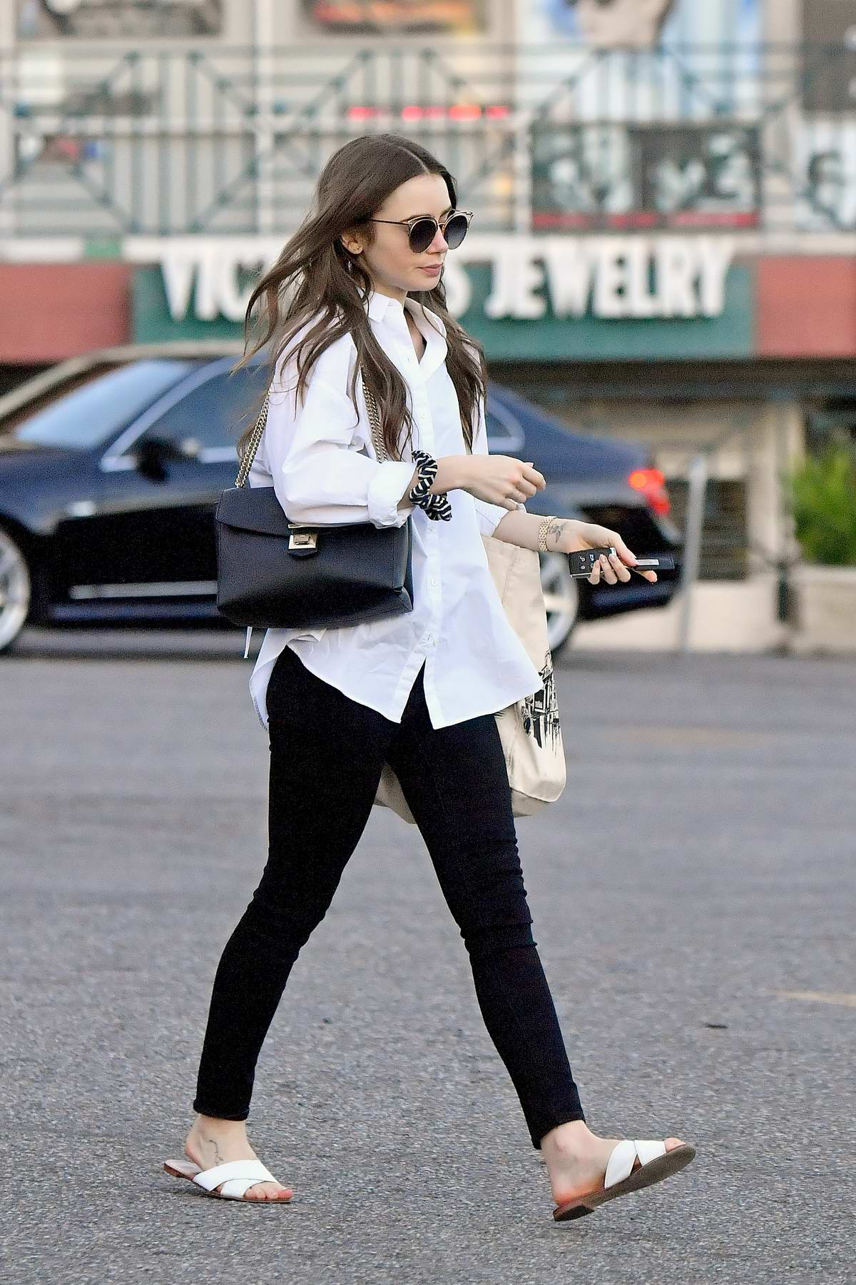 Lily Collins keeps it casual with a white shirt and black jeans while out shopping in West Hollywood, Los Angeles