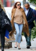 Lindsay Lohan seen wearing brown trench coat and studded jeans as she leaves her apartment in New York City