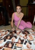 Lindsay Lohan signs some photos while waiting backstage at The Rachael Ray Show in New York City