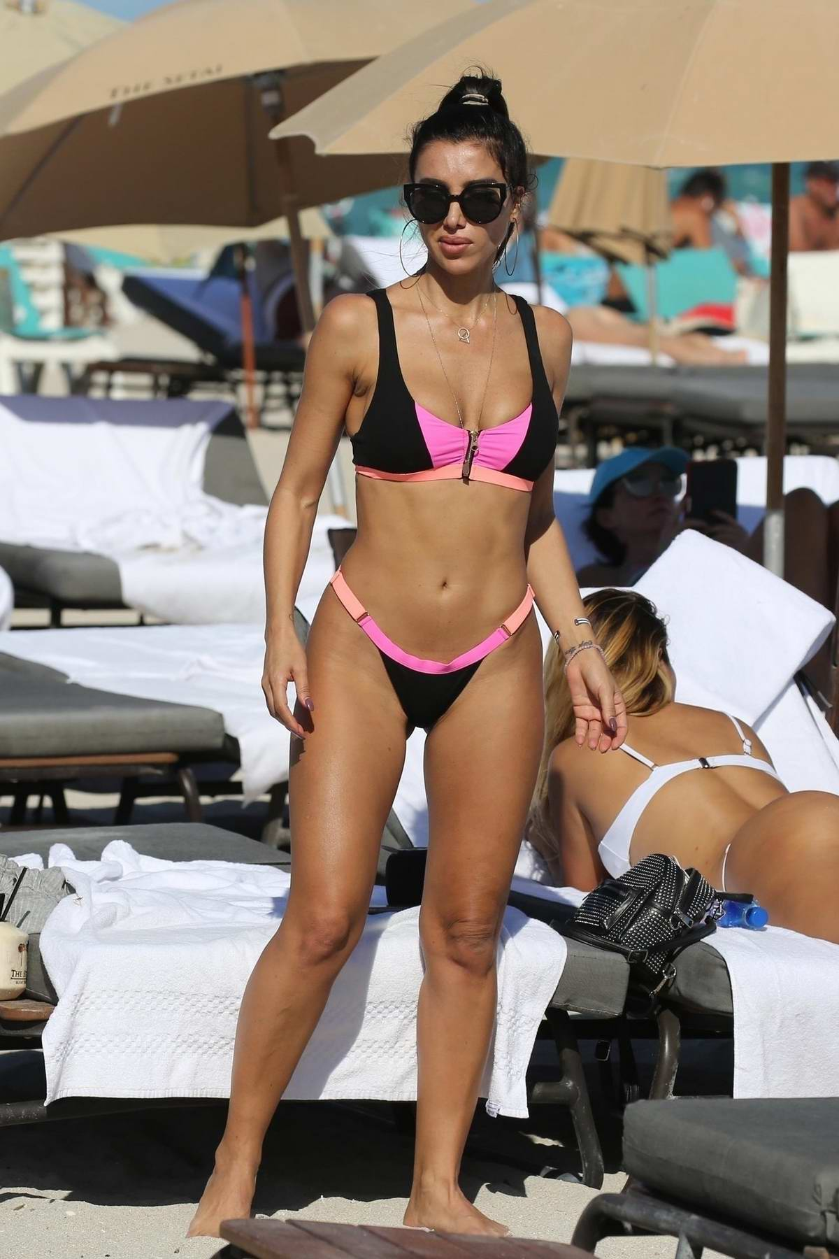 Metisha Schaefer puts on a pink and black bikini while enjoying the sun on Miami Beach, Florida