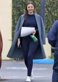 Miranda Kerr wears grey trench coat with blue sweatshirt and blue leggings while out running errands in Los Angeles