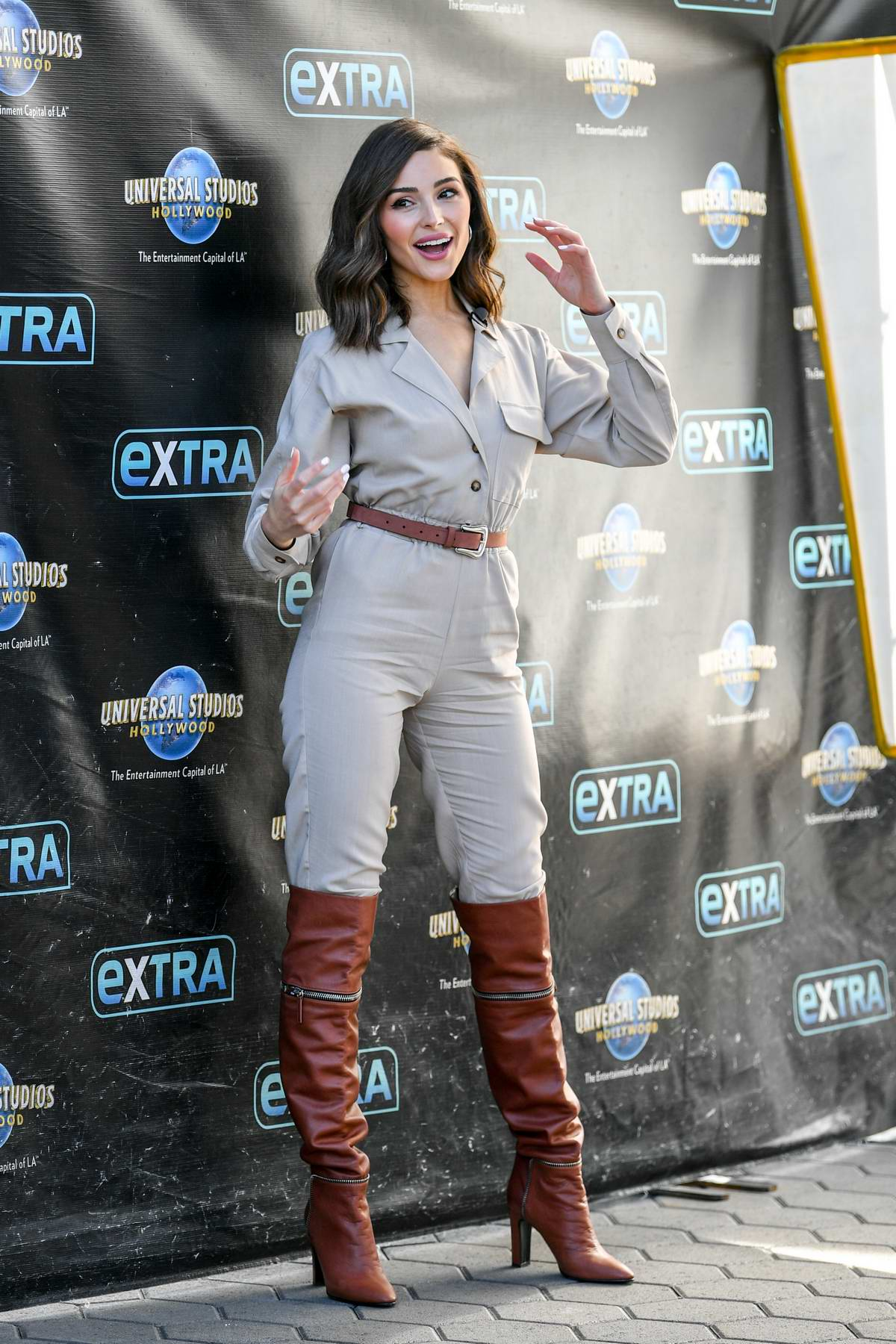 Olivia Culpo rocked a beige jumpsuit and knee high brown boots on the set of 'EXTRA' at Universal Studios in Universal City, California