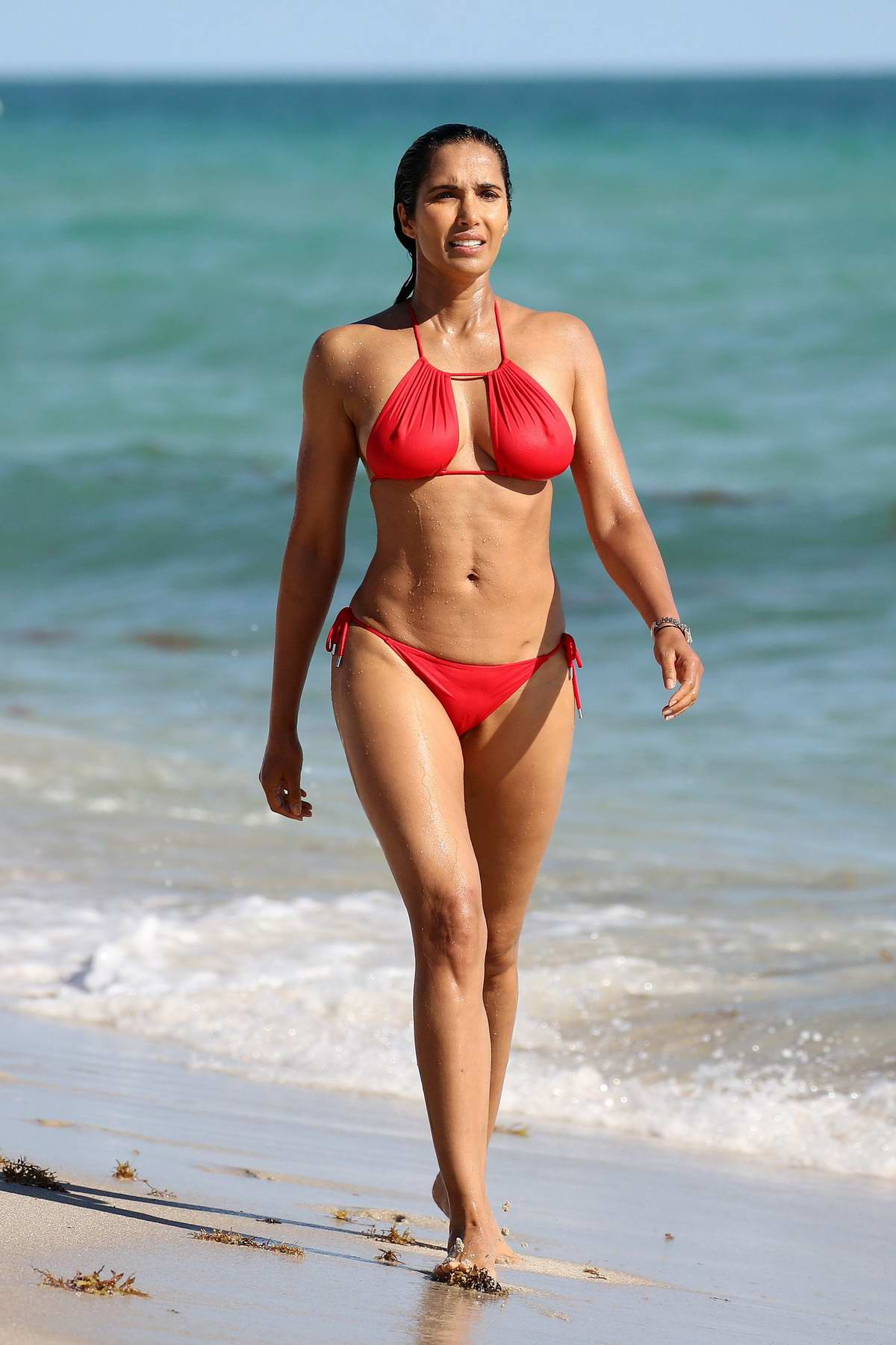 Padma Lakshmi sizzles in a red bikini as she hits the beach in Miami, Florida