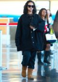 Rihanna wears a Raf Simmons denim jacket and Ugg Boots as she arrives at JFK airport in New York City