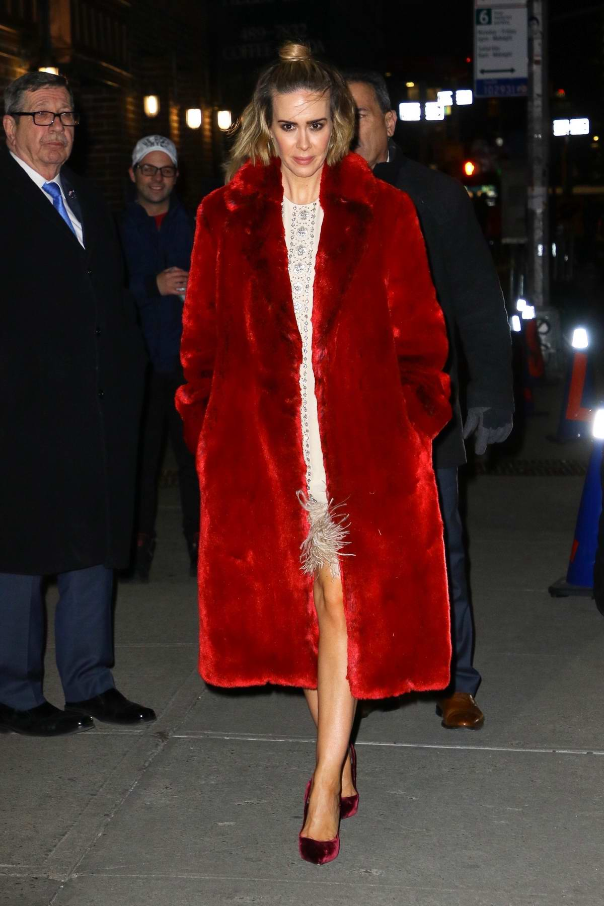 Sarah Paulson wears a red fur coat with a white dress as she arrives to The Late Show with Stephen Colbert in New York City