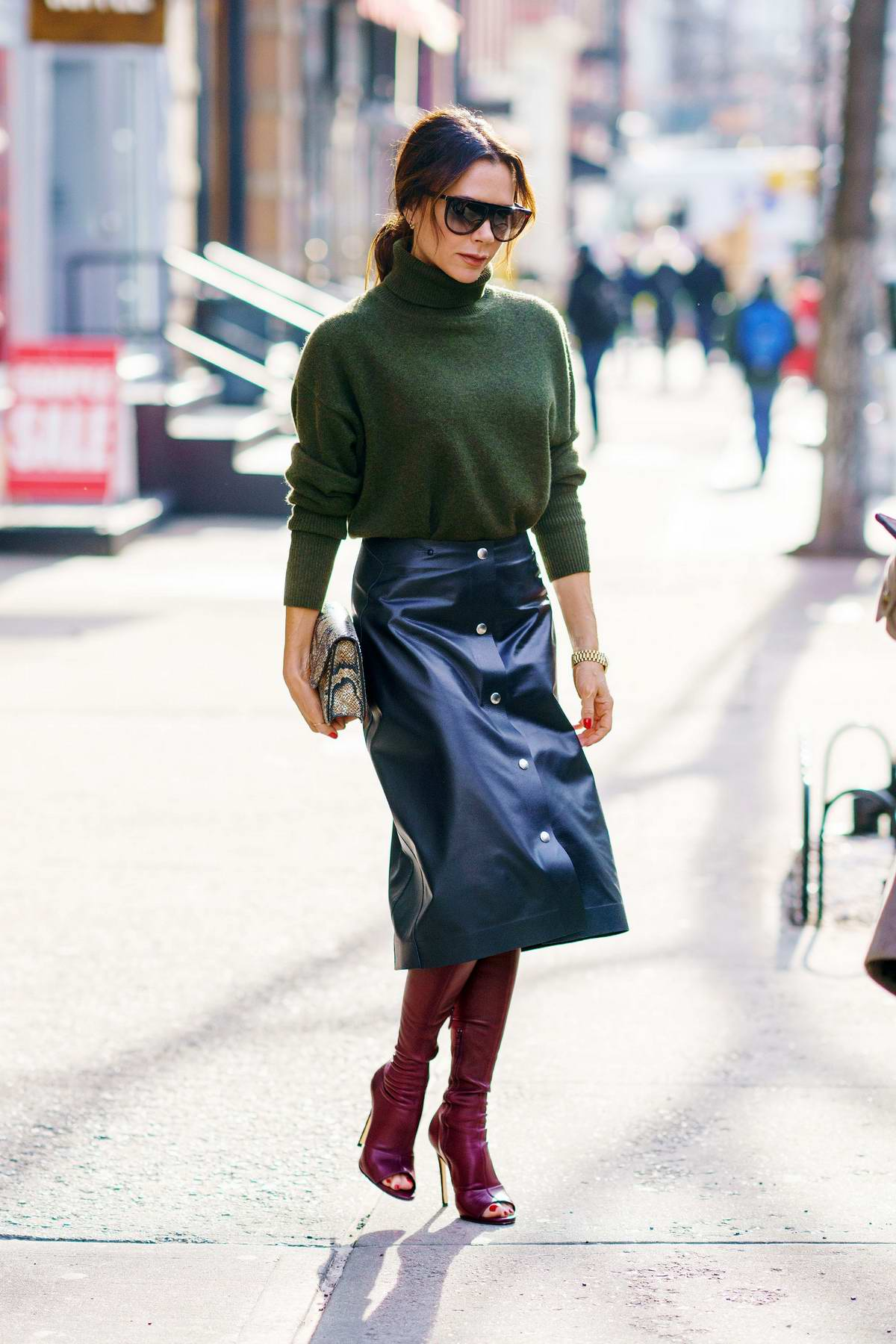 Victoria Beckham steps out wearing a green turtleneck, black leather skirt and maroon boots during a shopping trip in New York City