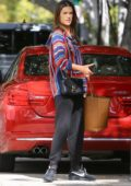Alessandra Ambrosio wore a colorful knit hoodie and black sweatpants while heading out with luggage in Santa Monica, California