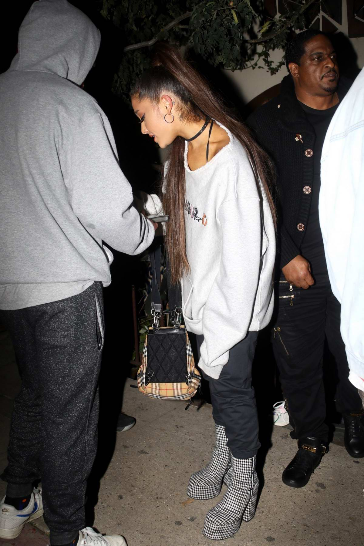 Ariana Grande tries to cover her face as she leaves Pace Restaurant in Los Angeles