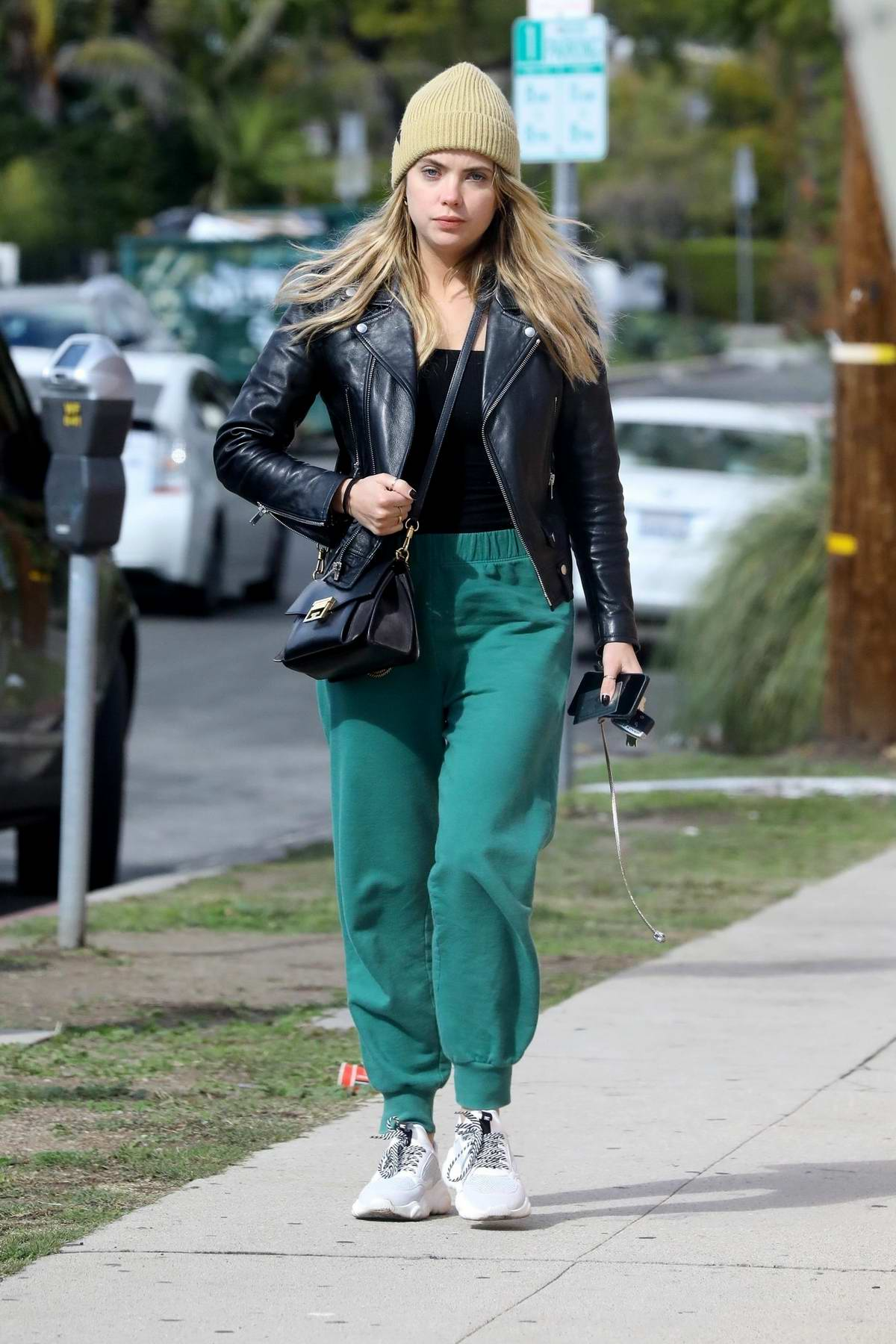 Ashley Benson steps out for a stroll while rocking teal sweatpants, black leather jacket and a beanie in Los Angeles