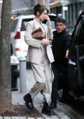 Bella Hadid wore a light grey suit with black boots as she leaves her apartment in New York City