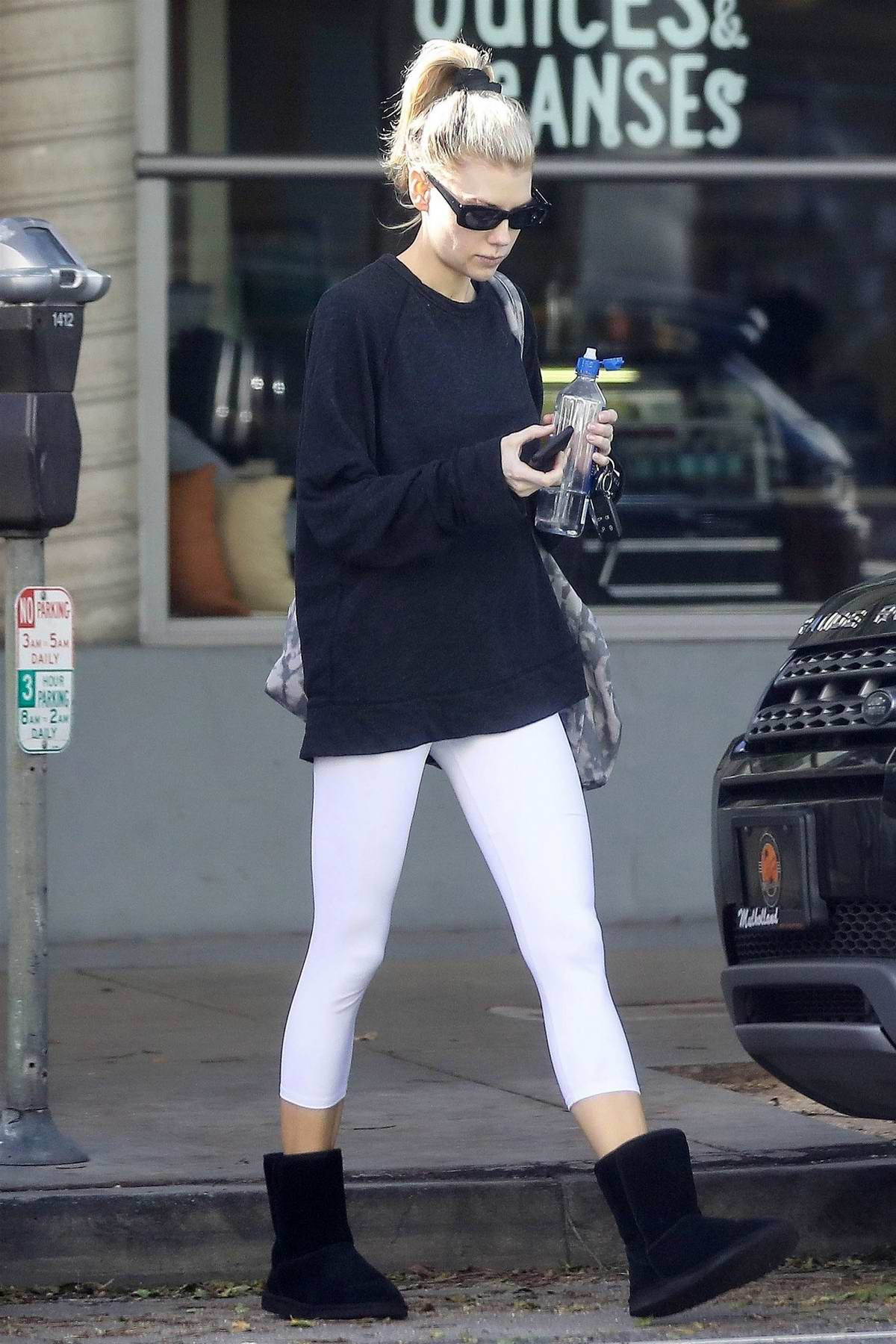 Charlotte Mckinney checks her phone as she leaves a hot yoga class in Santa Monica, California