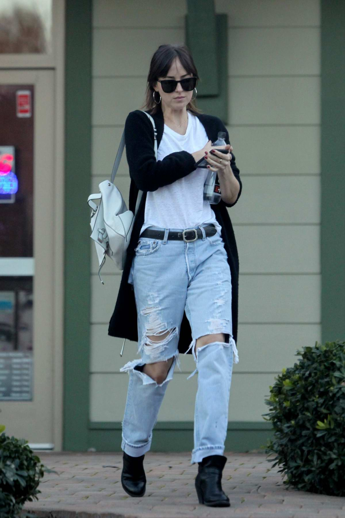 Dakota Johnson wears a white t-shirt, black cardigan and ripped jeans during her trip to a nail salon in Los Angeles