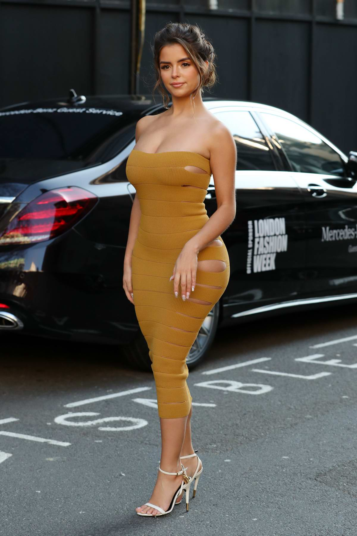 Demi Rose stuns in a mustard yellow strapless dress while out during London Fashion Week in London, UK
