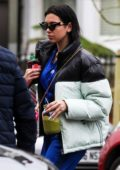 Dua Lipa sips on a green smoothie as she steps out wearing a blue Adidas tracksuit and puffer jacket in London, UK