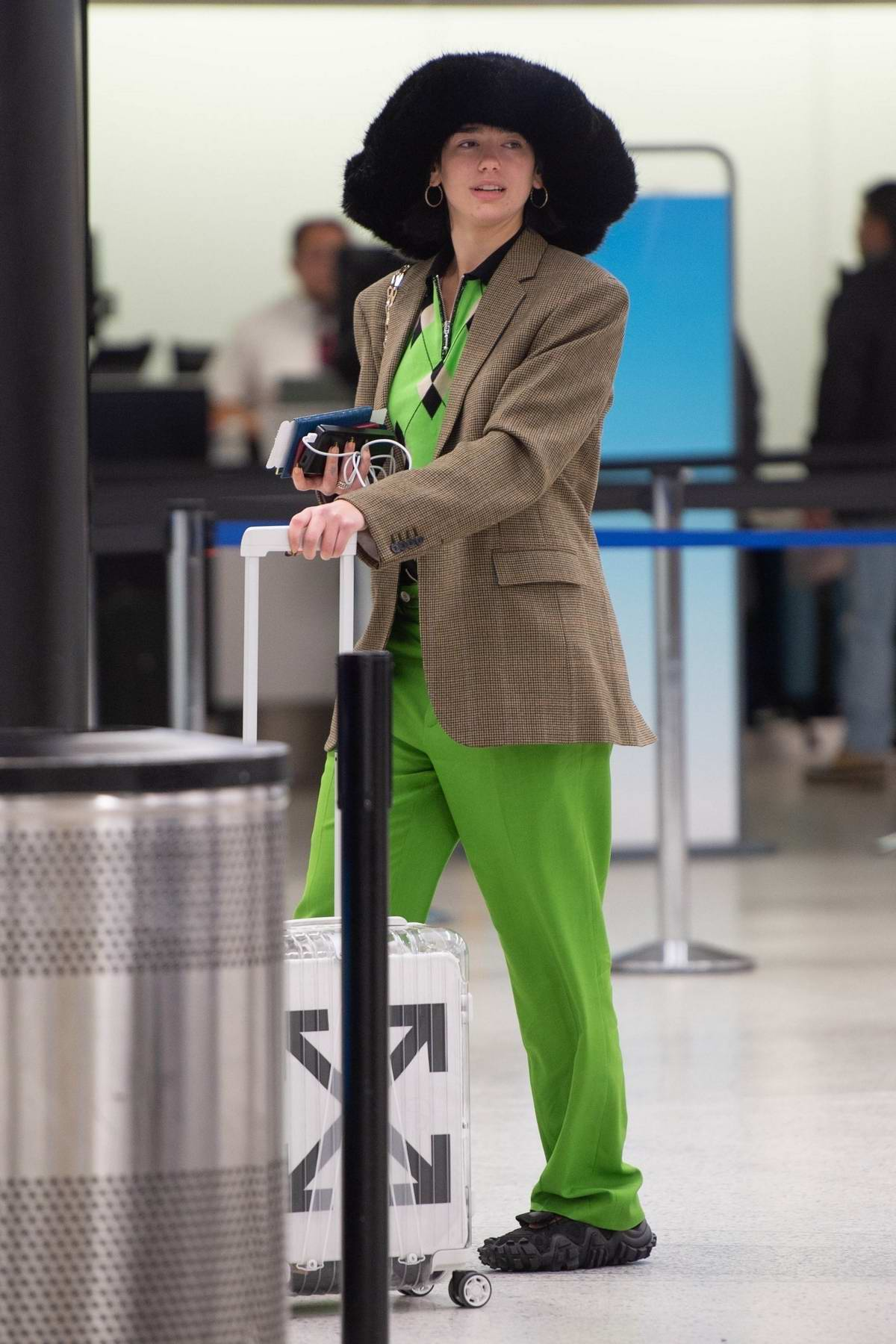 Dua Lipa wears a bright neon green suit and fur hat as arrives to catch a flight out of JFK in New York City