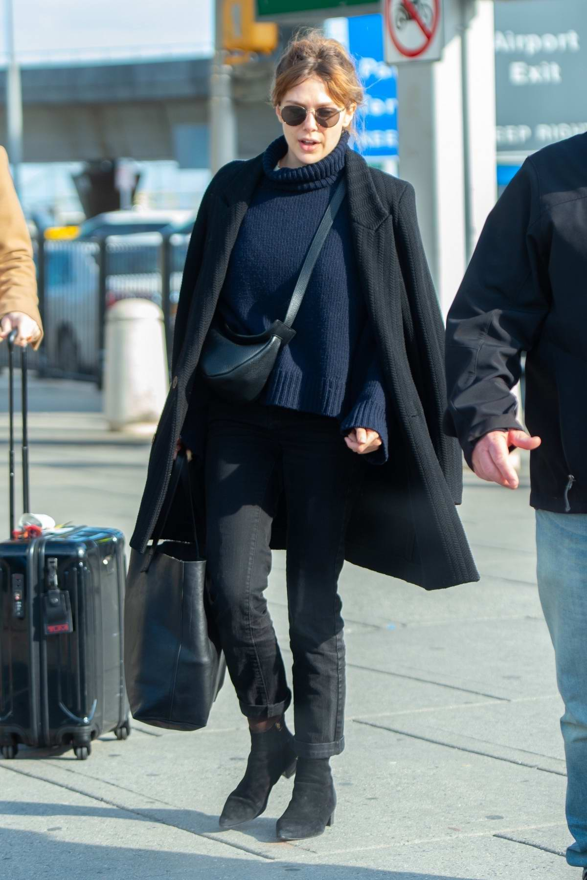 Elizabeth Olsen bundles up as she arrives at JFK airport to jet out of New York City