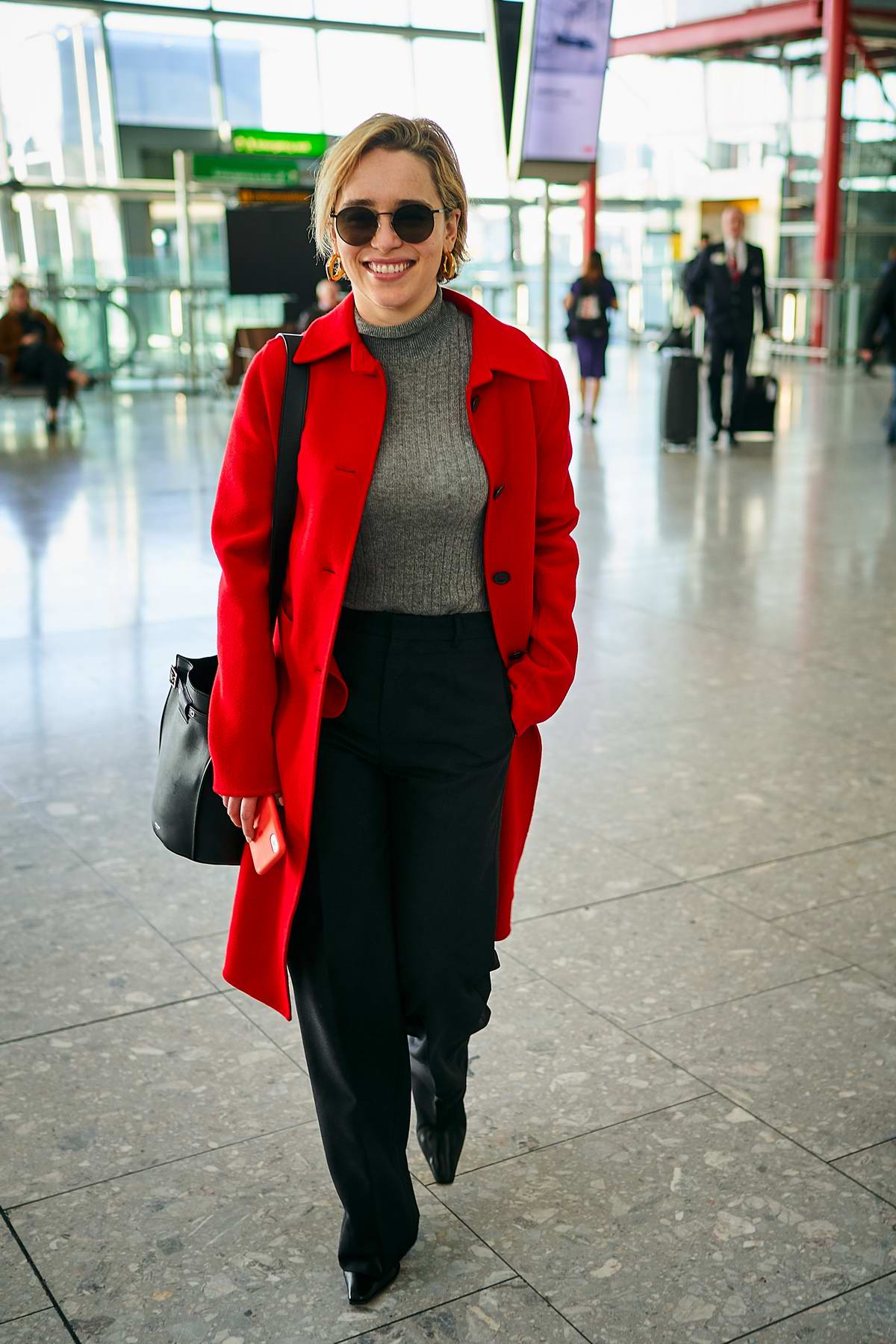 Emilia Clarke is all smiles as she flies out of Heathrow Airport in London, UK