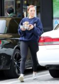 Francesca Eastwood wears a blue sweatshirt and black leggings while picking up smoothies from EarthBar in West Hollywood, Los Angeles