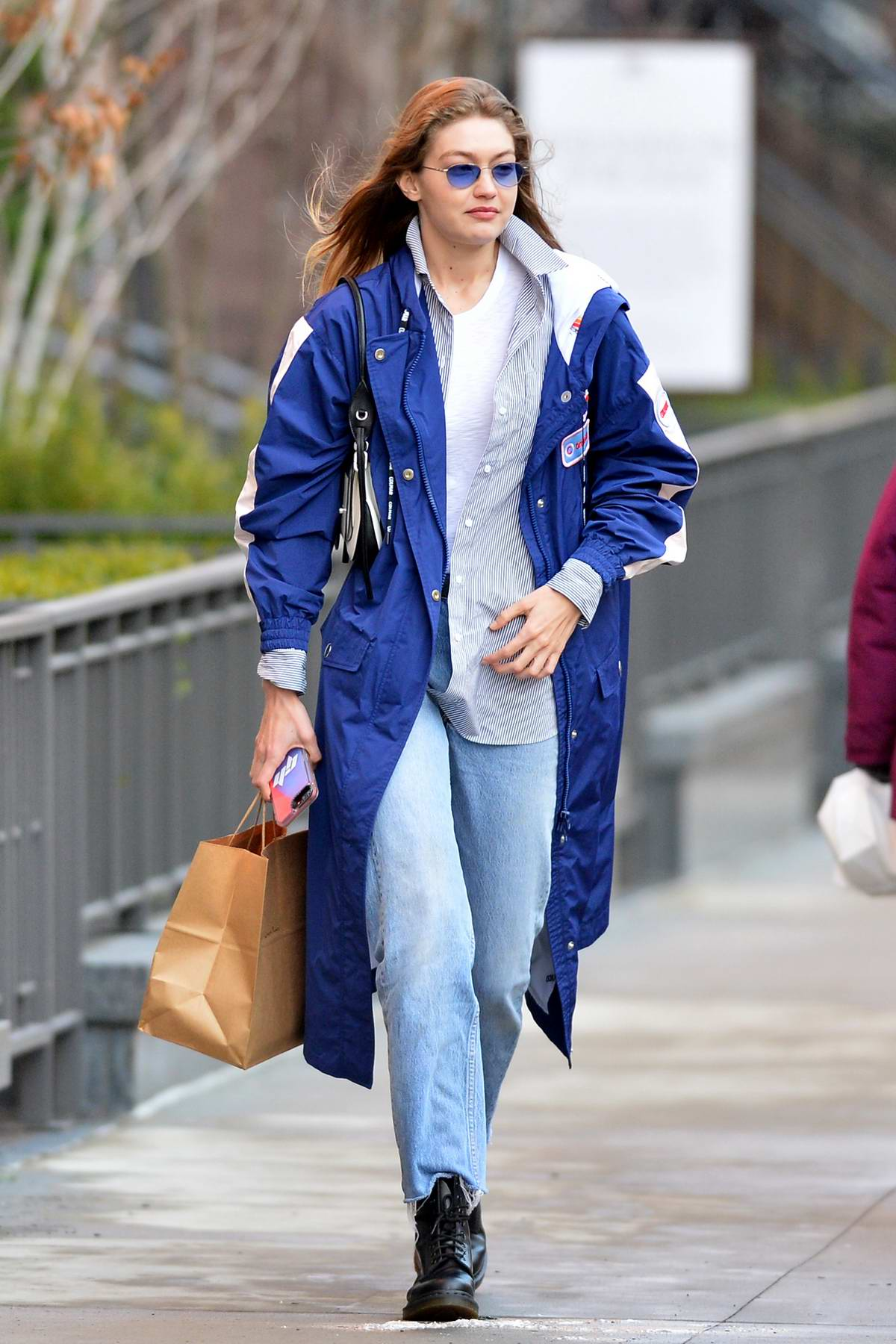 Gigi Hadid looks trendy in a long blue jacket with matching blue shades while out in New York City