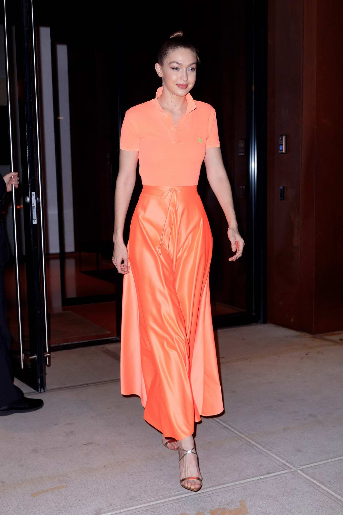 Gigi Hadid wears bright orange as she heads to Maybelline New York Fashion Week party in New York City