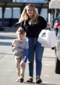 Hilary Duff juggles dinner bags and ice cream while coddling her son after he banged his shin, Los Angeles