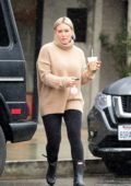 Hilary Duff wears a beige turtleneck sweater with black leggings and rain boots while running errands on a rainy day in Los Angeles