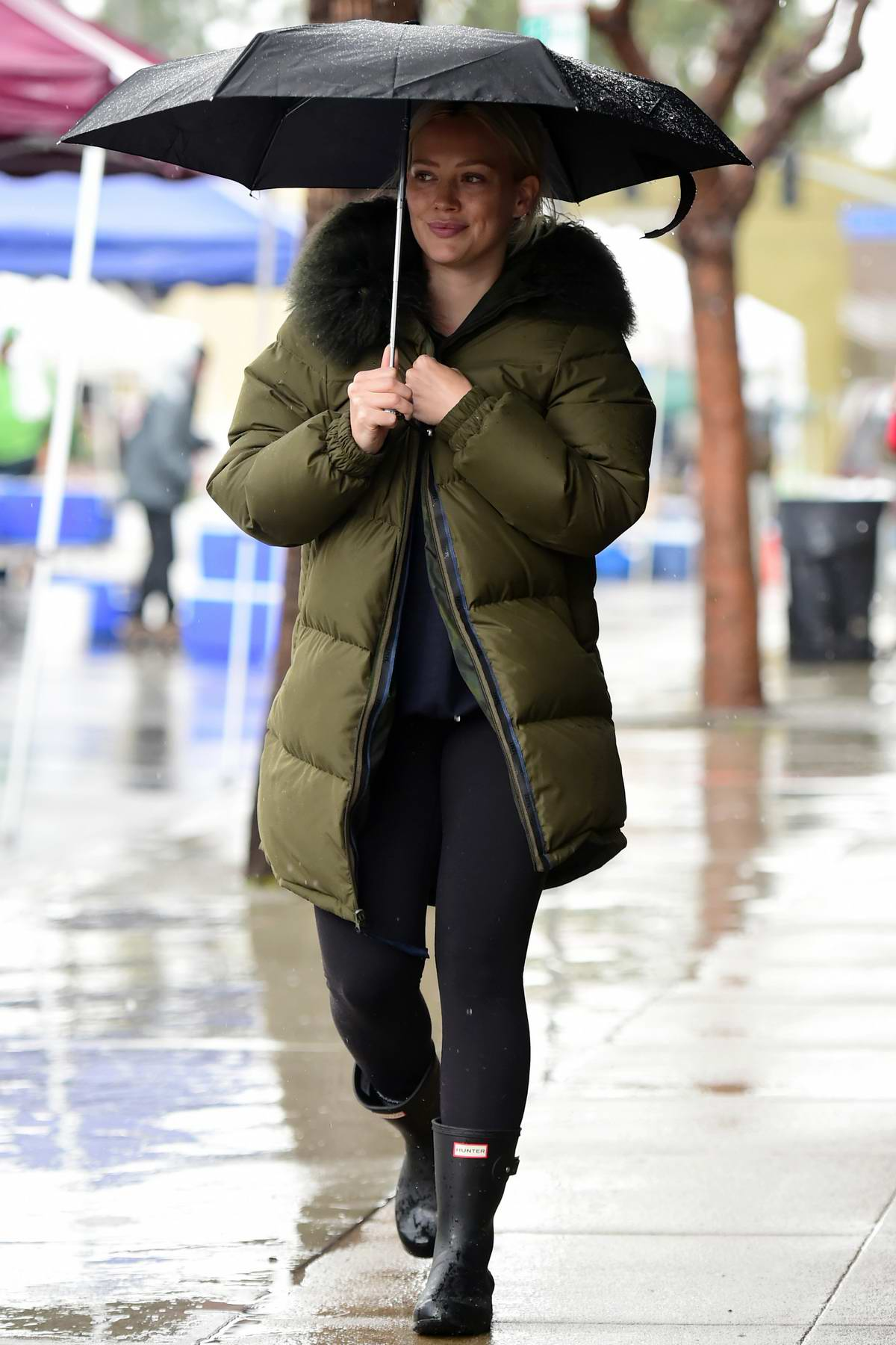 Hilary Duff wore a green puffer jacket, leggings and rain boots while out to pick up lunch to go from Joan's on Third in Studio City, Los Angeles