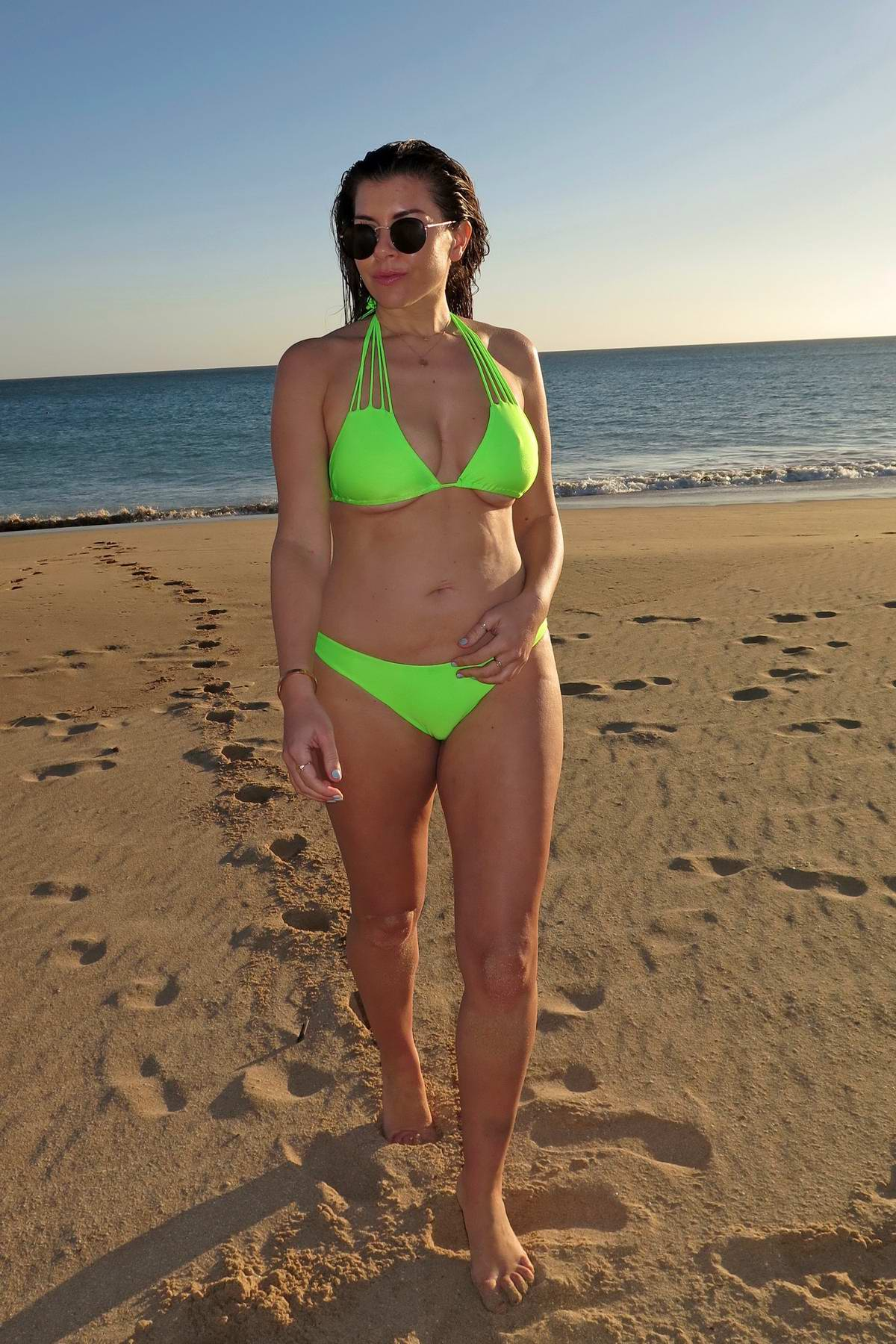 Imogen Thomas poses in a neon green bikini during a beach photoshoot for her own swimwear range in Faro, Portugal