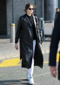 Kaia Gerber looks stylish in a black leather trench coat with grey Adidas sweatpants as she touches down at Malpensa Airport in Milan, Italy