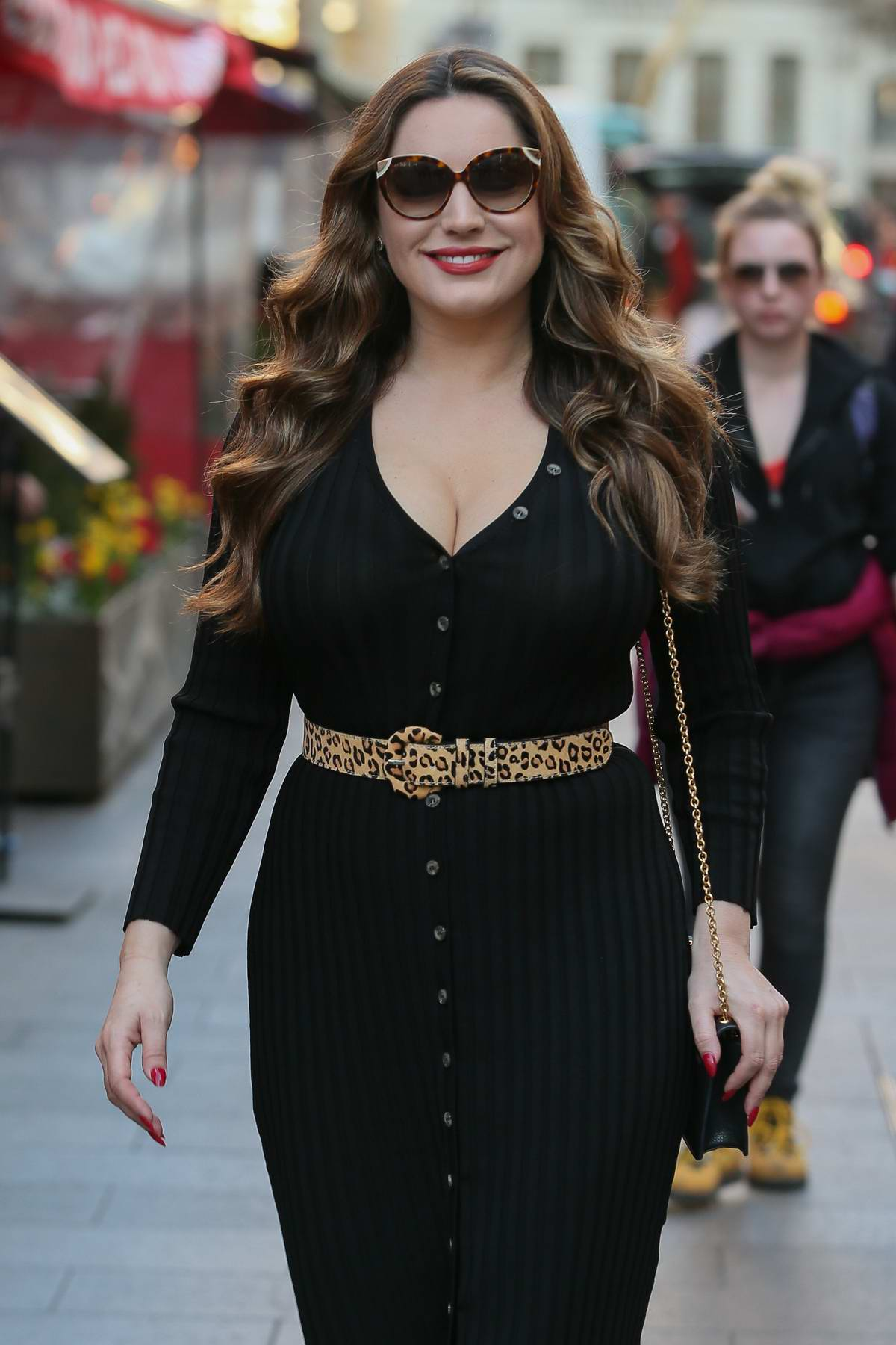 Kelly Brook dons a plunging black dress with leopard print heels and belt as she arrives for her show at Global Radio studios in London, UK