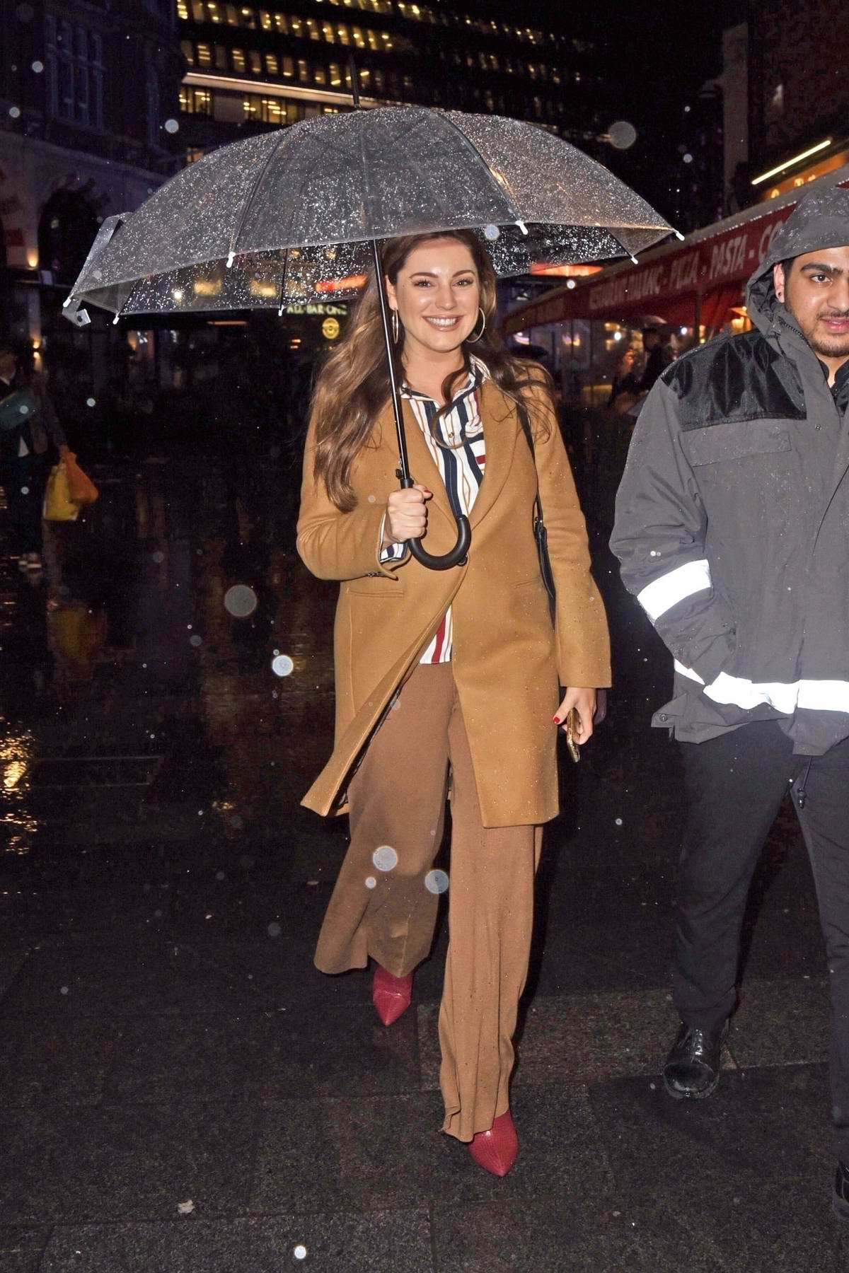 Kelly Brook is all smiles as she steps out in the rain holding a clear umbrella while leaving Global Radio studios in London, UK