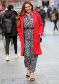 Kelly Brook is all smiles in a red coat and a busy patterned jumpsuit as she leaves Global Radio studios in London, UK